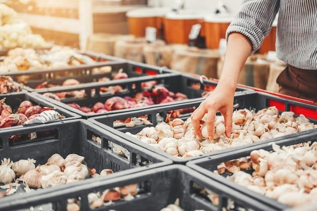 アジアの女性がスーパーで健康食品野菜や果物をショッピング Premium写真