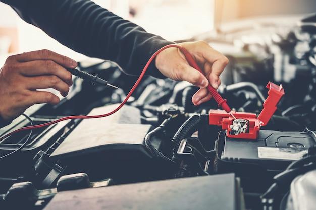 Техник руки автомеханика, работающего в автосервисе сервисное и техническое обслуживание автомобильного аккумулятора Premium Фотографии