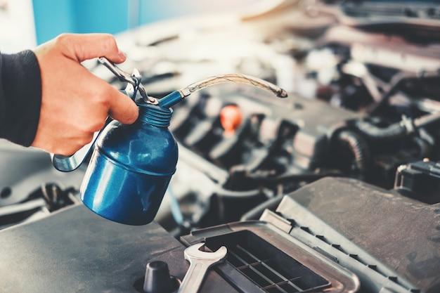 自動車修理サービスおよびメンテナンス車で働く自動車整備士の技術者の手 Premium写真