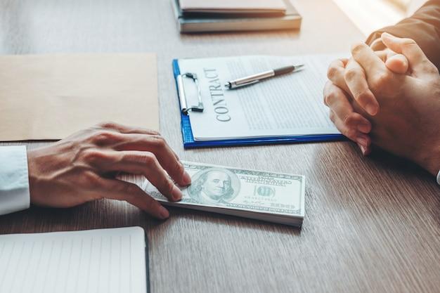 Бизнесмен дает взяточничество коррупции долларовых купюр бизнес-менеджеру для заключения контракта Premium Фотографии