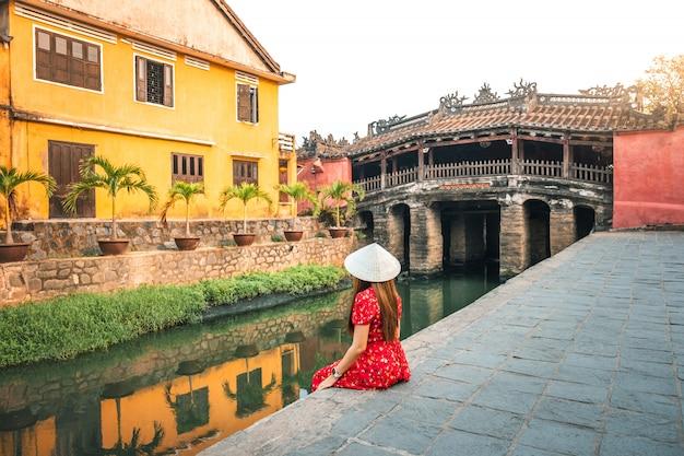 ベトナムのホイアンにある日本の屋根付き橋で旅行する女性 Premium写真
