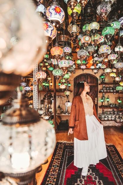 素晴らしい伝統的な手作りトルコランプを選択する幸せな旅行女性 Premium写真