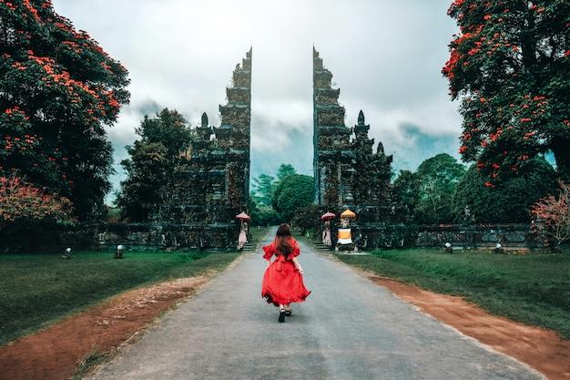 インドネシアバリ島ゲイツヒンドゥー寺院で走っている旅行者の女性 Premium写真