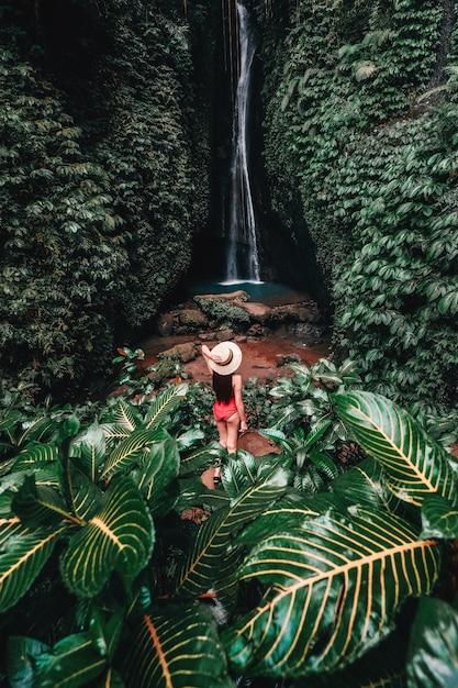 美しい湖湖の滝での生活を楽しんでバリ島の熱帯雨林を持つ若い女性を旅行します。 Premium写真