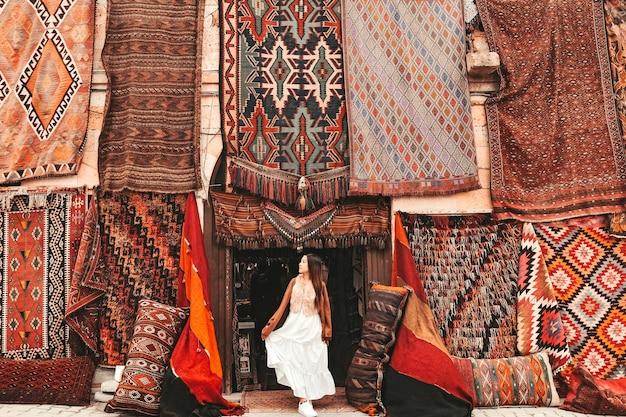 地元のカーペットショップ、ギョレメで驚くほどカラフルなカーペットを持つ幸せな旅行女性。カッパドキアトルコ Premium写真