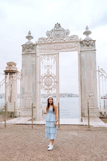 Путешествие женщина с видом на дворец долмабахче стамбул городской пейзаж плавучие туристические катера в босфор, стамбул Premium Фотографии