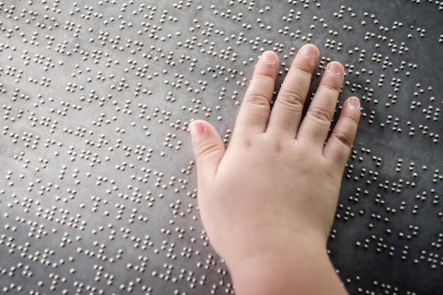 盲目の子供の手が金属板の点字を触って理解する Premium写真