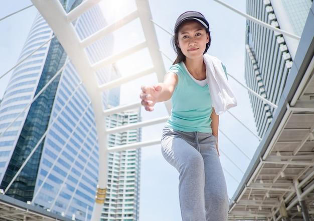 彼女の手に届くスポーツ少女と立ち上がるのを手伝ってください。 Premium写真