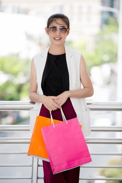 Красивая азиатская девушка гуляя и ходя по магазинам в городской улице города Premium Фотографии