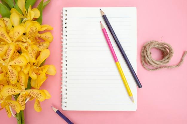開いているノートブック紙、黄色の蘭の花、色鉛筆、ピンクの背景の自然ロープの平面図またはフラットレイアウト。 Premium写真