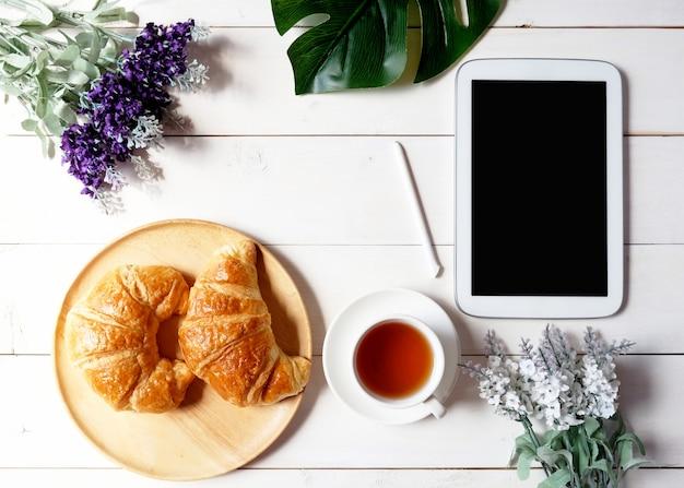 タブレット、緑の葉、花、白い木製の背景にクロワッサンと木製皿とお茶のカップ。 Premium写真