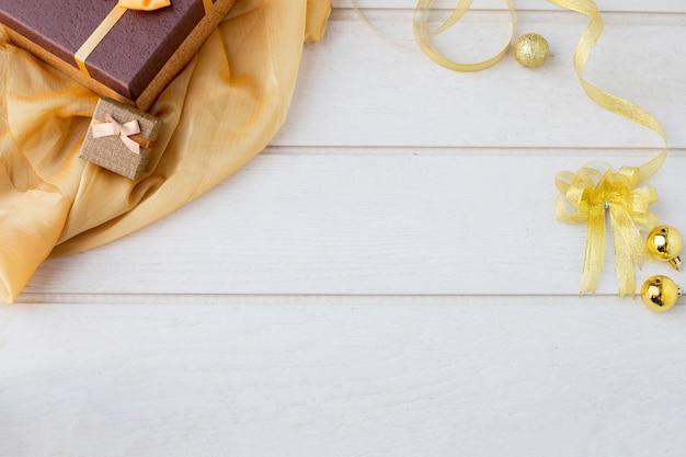 クリスマスの装飾と黄金のテーブルクロスと白のトップテクスチャの背景。 Premium写真