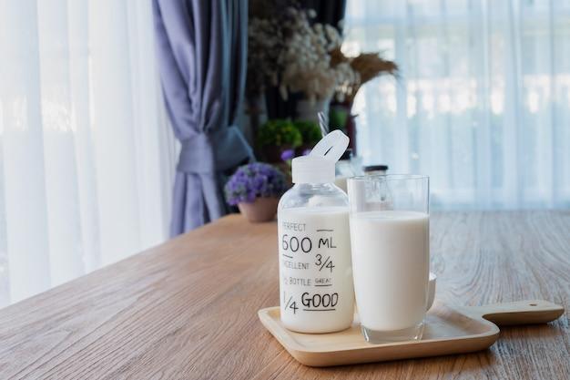 Деревянный стол с стакан молока, бутылка молока и ретро будильник в гостиной. Premium Фотографии