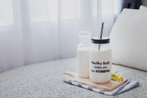 白いカーテン窓のあるリビングルームのベッドの上の牛乳と牛乳のガラス瓶。 Premium写真