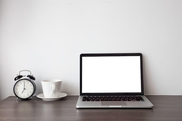 ノートパソコン、ノートブック、ホットコーヒーカップ、白いセメントの背景にレトロな黒い時計に空白の画面を持つ木製のオフィスのテーブル。 Premium写真