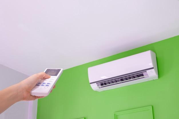 人間の手がエアコンのスイッチをオンにするリモコンを押します。 Premium写真