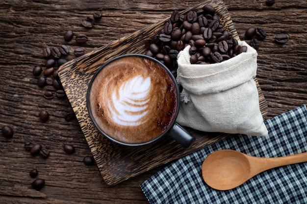 Чашка кофе латте с зернами кофе на деревянный стол. Premium Фотографии
