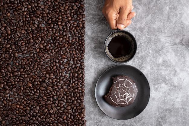 人間の手は、セメントテクスチャ背景にコーヒー豆とコーヒーのマグカップとチョコレートケーキを保持します。 Premium写真