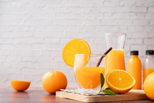 絞りたてのオレンジジュースのグラス、砂糖無添加の木製テーブル。 Premium写真