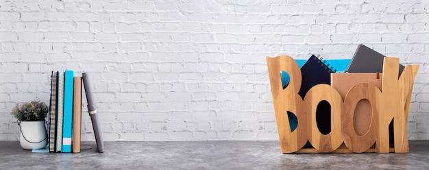 Книжная полка с книгами в деревянной коробке на кирпичной стене Premium Фотографии