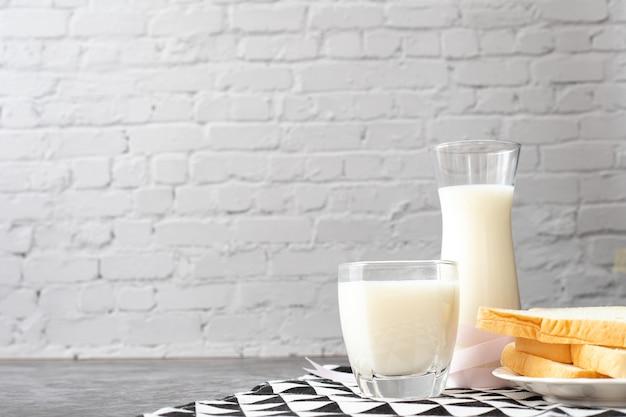 ミルクのガラス、ミルクの水差しと朝食用のテーブル。 Premium写真