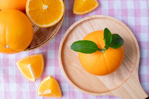 Нарезанный оранжевый плод на розовой скатерти текстуру фона Premium Фотографии