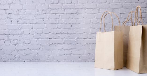 レンガ壁のテクスチャ背景にコピースペースを持つクラフトペーパーショッピングバッグ。 Premium写真