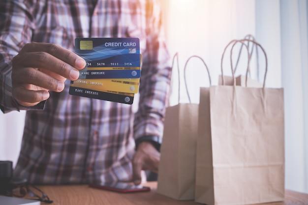 人間の手はクラフト紙袋でクレジットカードを保持します。 Premium写真