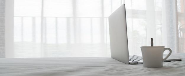 ホットドリンクと寝室の白いベッドの上のノートパソコンの側 Premium写真