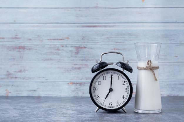 Банка молока с классическими часами на кухонном столе, концепция утреннего напитка. Premium Фотографии
