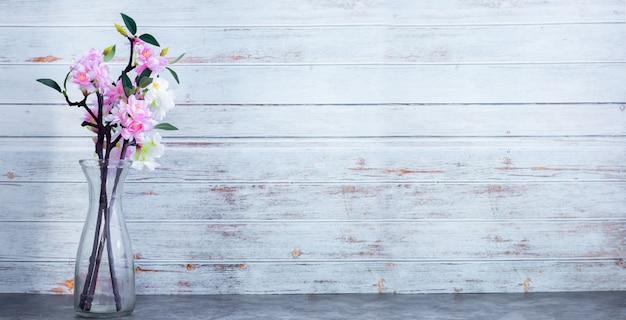 Стеклянный горшок с вишней на деревянной стене текстуры фона, копией пространства. Premium Фотографии