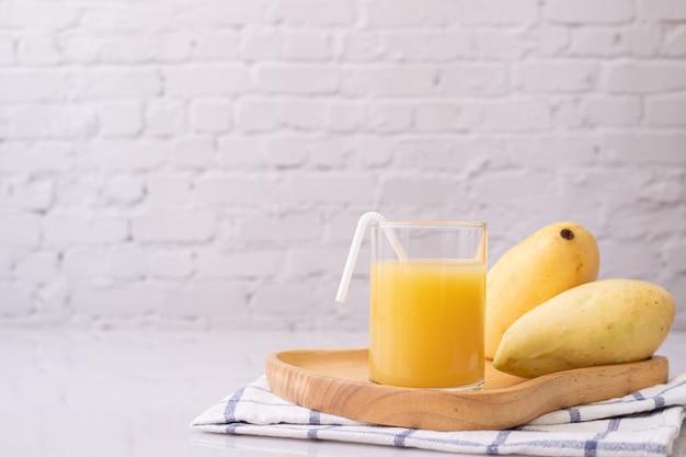 Стекло сока манго на кухонном столе. Premium Фотографии