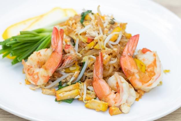 白い皿にエビパッドタイ(タイの郷土料理) Premium写真