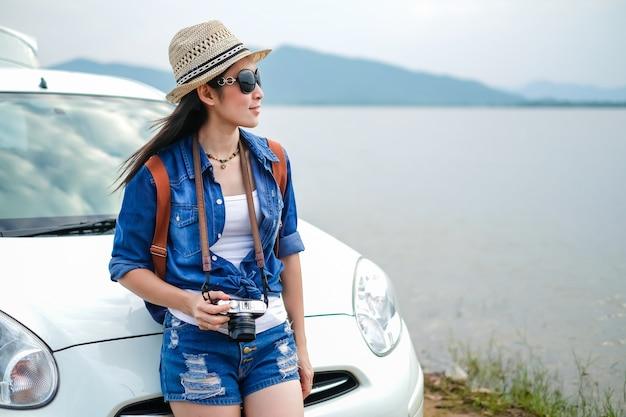 Женщина путешественника, стоящего рядом с автомобилем, и смотрит на природу у озера Premium Фотографии