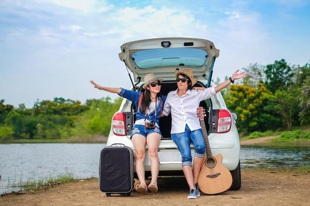Пара путешественник, сидя на хэтчбек автомобиля и наслаждаясь видом на природу недалеко от озера Premium Фотографии