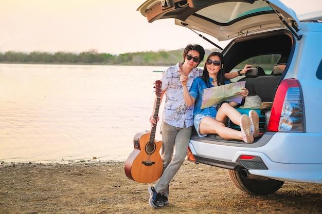 Пары путешественника сидя на хэтчбеке автомобиля и играя гитару около дороги во время праздника. Premium Фотографии
