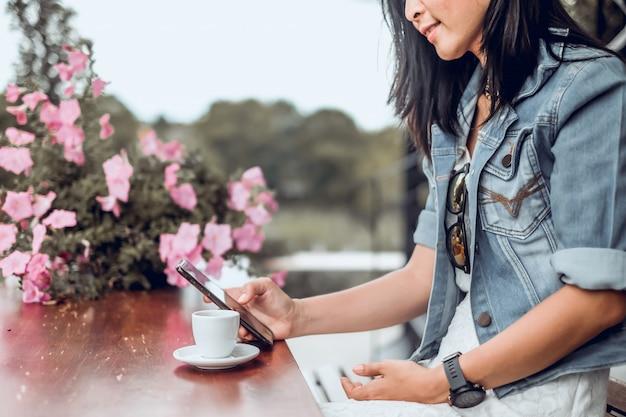 アジアの女性がコーヒーショップに座っていると携帯電話を使用して Premium写真