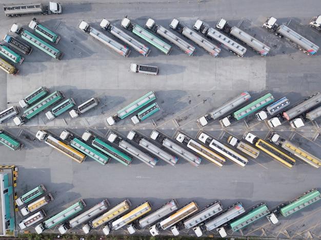 石油トラックの空撮は、石油の輸送を待っている駐車場に駐車されています。 Premium写真