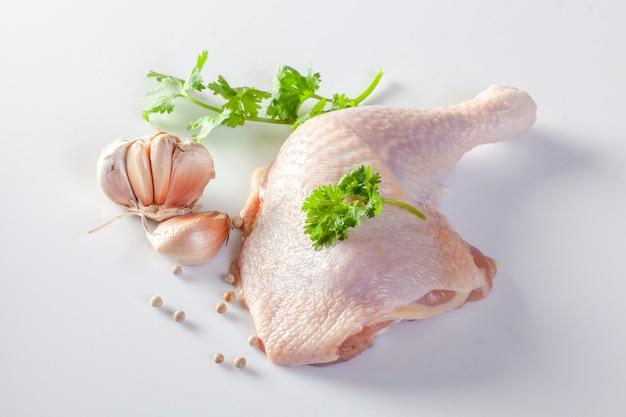 Сырые куриные ножки со специями и овощами на белом фоне Premium Фотографии