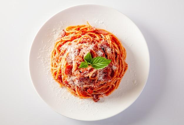 白い背景の上の皿にスパゲッティ Premium写真