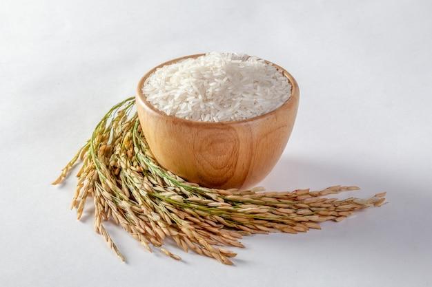 Тайский рис жасмин в деревянной миске и изолированный рис на белом фоне Premium Фотографии