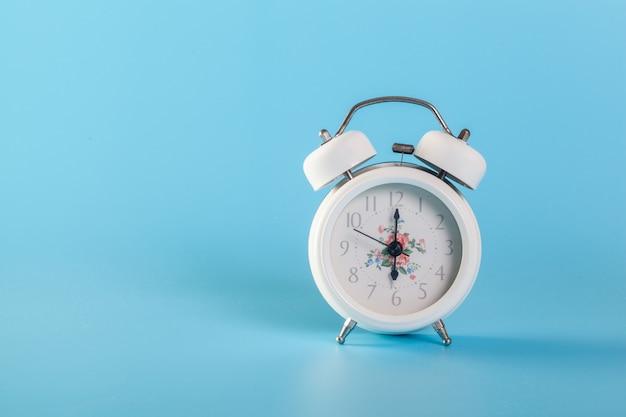 水色の壁に白い時計 Premium写真