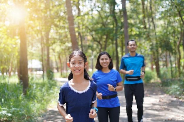 Азиатская семья, тренирующаяся и бегающая трусцой вместе в парке Premium Фотографии