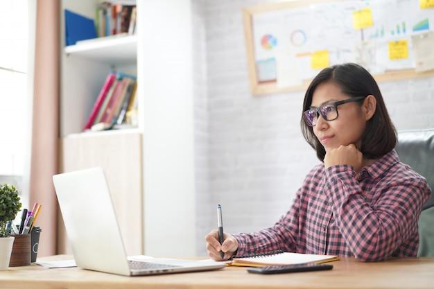 アジア女性実業家のラップトップコンピューターで読む Premium写真