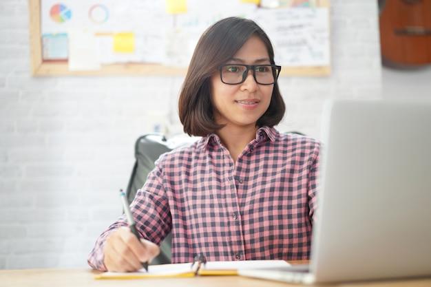 アジアの実業家のネットブック紙をチェックしながらラップトップコンピューターで読む Premium写真
