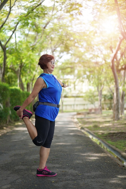 アジアの年配の女性は公園で音楽を聴きながら筋肉を伸ばします。 Premium写真