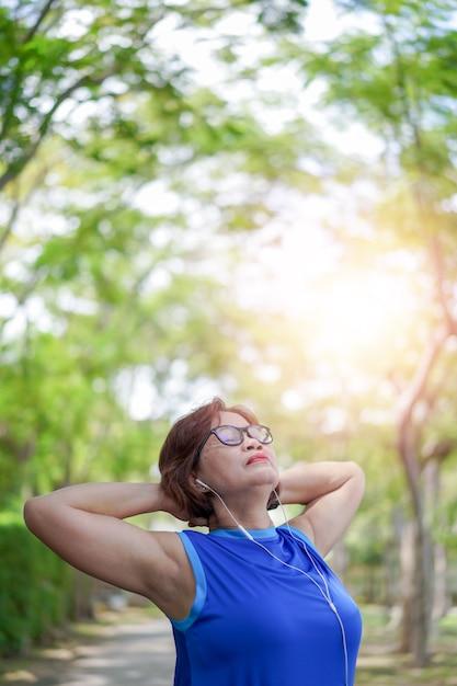 アジアのシニア女性リラックスした公園で音楽を聴く Premium写真