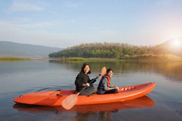 Мать и дочь гребная лодка на спокойных водах Premium Фотографии
