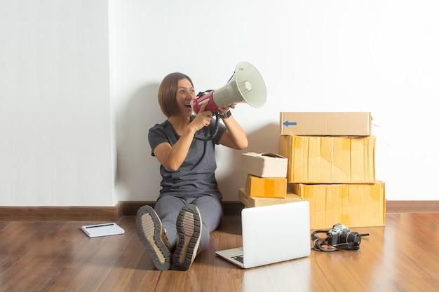 自宅からラップトップコンピューターとメガホンを保持している女性 Premium写真