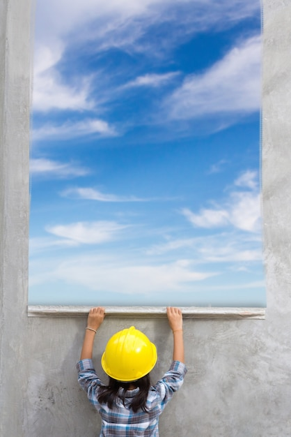 Маленькая девочка держит штукатурные инструменты, ремонт дома. с росписью голубого неба облаками Premium Фотографии